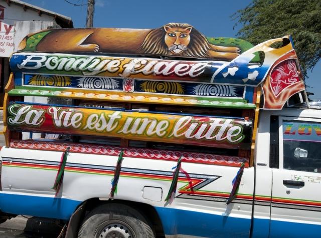 """Foto: """"Livet er en kamp"""" står skrevet på fargerik bil."""